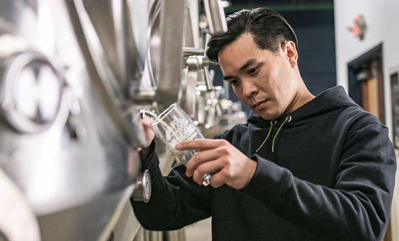 Brewer pours a cold beer while wearing Leatherman Basic Pullover Hoodie in black.
