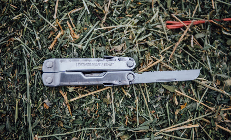 Leatherman stainless steel Rebar multi-tool on grass, knife blade open