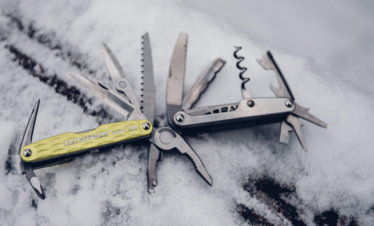 Leatherman juice xe6 multi-tool on snow, green, fanned out, 18 tools