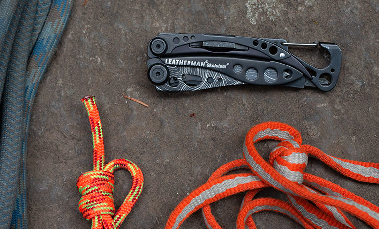 Leatherman Skeletool multi-tool, topo print, closed with rock climbing gear