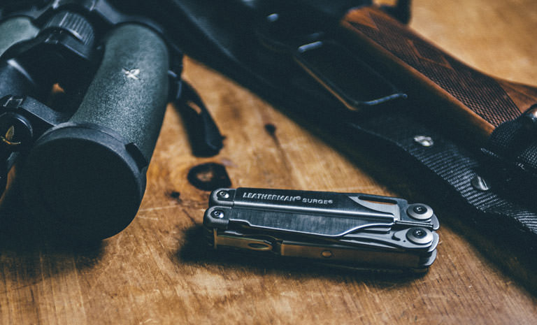 Leatherman surge multi-tool on wooden table, next to hunting gear